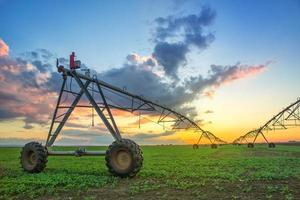 automatisiertes landwirtschaftliches Bewässerungssystem bei Sonnenuntergang foto