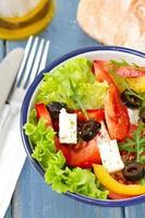 Salat in der Schüssel mit Brot und Öl auf blauem Hintergrund foto
