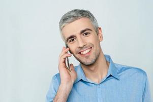 Mann mittleren Alters, der auf dem Handy spricht foto