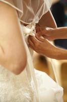 Braut beim Festziehen des Kleides foto