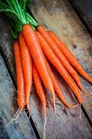 Bauernhof hob organische Karotten auf hölzernem Hintergrund an