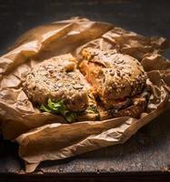 Brötchen mit Huhn, Käse Salat zerknittert Papier rustikalen Holz Hintergrund