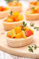 Törtchen mit geröstetem Gemüse und Thymian auf einem Holzbrett foto