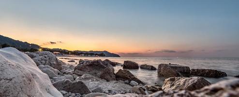 Sonnenuntergang über Meer und Felsen.