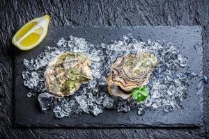 leckere Austern auf schwarzem Felsen foto
