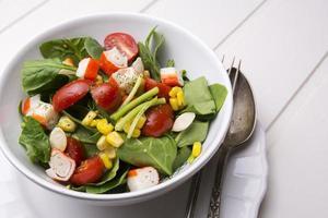 Spinatsalat mit Kirschtomaten und Mais in der Schüssel foto