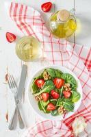 Salat mit Babyspinat, Erdbeere, Nüssen, Öl, Brot, karierter Serviette foto