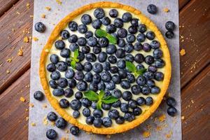 Blaubeertorte auf Weinlesehölzernhintergrund foto