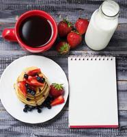 Frühstück mit Pfannkuchen, Kaffee, Milch und offenem Notizbuch