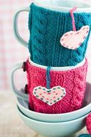 zwei blaue Tassen in blauem und rosa Pullover mit Herzen