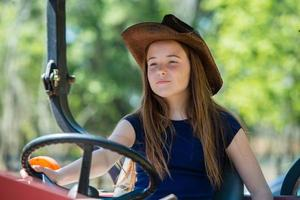 Bauernmädchen, das einen Traktor fährt foto