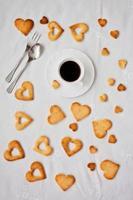 süße Kekse in Herzform und Tasse Kaffee foto