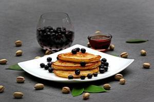 Pfannkuchen mit schwarzen Beeren und goldenem Sirup foto