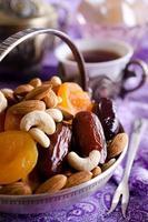 Mandeln, getrocknete Aprikosen, Cashewnüsse, Datteln, in einer Metallschale liegend foto