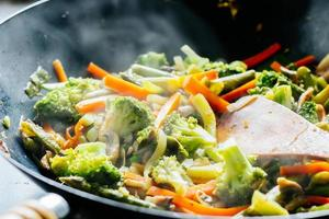 Wok unter Rühren mit Gemüse anbraten foto