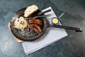 4 geröstete Nürnberger Bratwurste / Würstchen mit Sauerkraut in einer Pfanne.