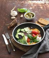 Pfanne mit Spiegeleiern, Salami, Spargel, Kirschtomaten mit Brot foto
