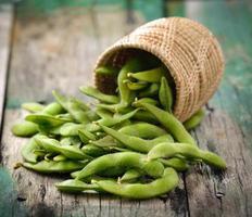 grüne Sojabohnen im Korb auf Holz foto