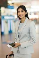 junge Geschäftsfrau, die im Flughafen steht foto
