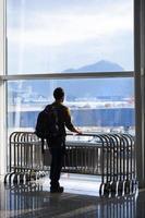 junger Mann am Flughafen macht Urlaub foto