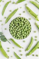 grüne Erbsen in der weißen Schüssel auf hölzernem Hintergrund foto
