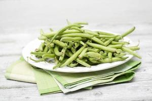 rohe grüne Bohnen (Phaseolus vulgaris) auf Teller foto