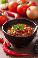 mexikanische Chili con Carne in schwarzer Platte mit Zutaten foto
