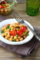 Kichererbsen mit Tomaten und Zwiebeln auf einem Teller foto