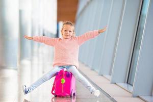 entzückendes kleines Mädchen, das Spaß im Flughafen hat, der auf Koffer sitzt foto