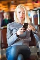 weiblicher Reisender, der Handy während des Wartens benutzt. foto