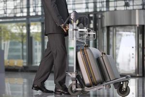 Geschäftsmann, der mit seinem Gepäck am Flughafen steht. foto