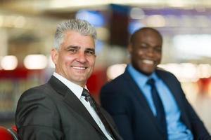 Geschäftsmann mittleren Alters und Kollege am Flughafen foto