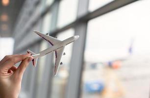 Nahaufnahmehand, die ein Flugzeugmodell hält foto