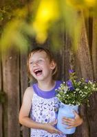 süßes kleines Mädchen mit Blumen lachen foto