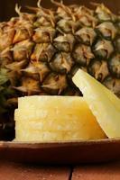 Dessertananas auf einem Holzteller geschnitten foto