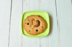 Mandel-Keks und grüner Teller auf Holztisch. foto