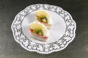 süßer Kuchen mit Kiwi und Ananas auf grauem Hintergrund