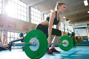 Frau in einem Fitnessstudio, das schwere Gewichtsübungen macht foto