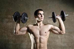 junger Mann, der Gewichte hebt foto