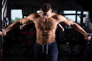 junger Bodybuilder mit Fitnessgeräten foto