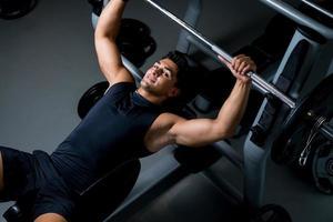 Der hübsche junge Bodybuilder bereitet sich lächelnd auf das Training vor