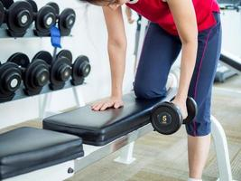 Frau, die mit dem Anheben der Hantel im Fitnessstudio trainiert foto