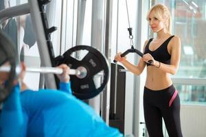 Frau, die Gewichte im Fitnessclub hebt foto