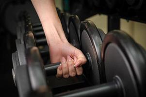 weibliche Hand, die Hantel hält