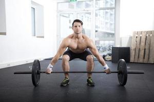 Athlet greift nach der Langhantel