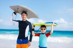 Vater und Sohn mit Surfbrettern foto