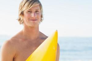 schöner Mann mit seinem Surfbrett, das in die Kamera lächelt