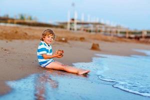 kleiner Junge, der Spaß mit Sandburg durch Ozean hat