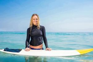Frau mit einem Surfbrett, das in die Kamera lächelt