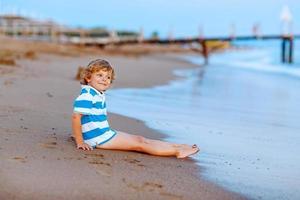 kleiner Junge, der Spaß mit Sandburg durch Ozean hat foto